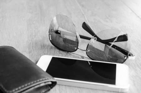 billfold: a set of tinted sunglasses and smartphone, leather wallet on wooden background - black and white effect style - with selective focus