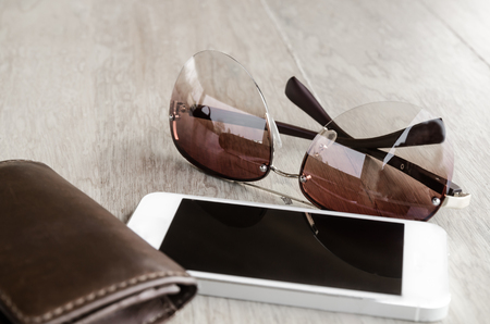 tinted: a set of tinted sunglasses and smartphone, leather wallet on wooden background-with selective focus
