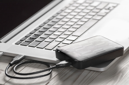 laptop computer with blank screen connecting to black external hard drive, External hard disk and laptop computer, with selective focus