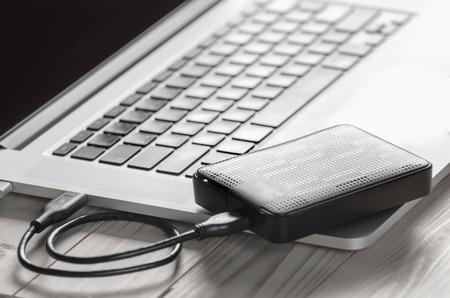 ordenador portátil con pantalla en blanco para conectar un disco duro externo negro, disco duro externo y el ordenador portátil, con el foco selectivo
