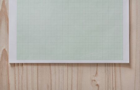 draftsman: graph paper with square background,close up blank graph paper on wooden desk with copy space for text