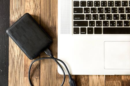 portable hard disk: portable hard drive and laptop computer, External hard disk and laptop computer, with selective focus