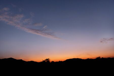 silhoutted: Quarter Moon rising behind silhoutted dark mountain Stock Photo