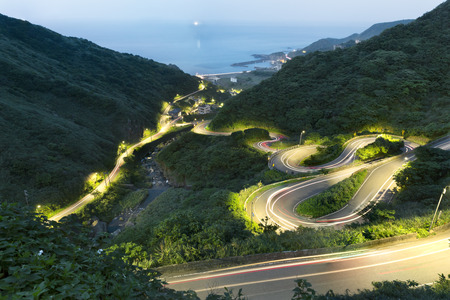 A curvy road through the grassy hills at twilight , Jiufen - Taiwan Stock Photo