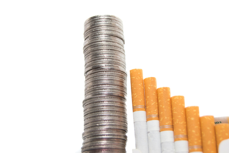 Rising expenses concept of cigarettes and coins isolated on white