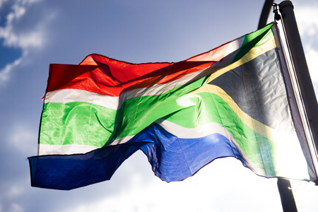 Waving flag from South-Africa with sun shining behind it against sky 版權商用圖片
