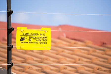 Secure electric fencing installed on residential wall and a blurred roof of a house in the background with yellow danger sign that warns about elecrical shock in Afrikaans, English and IsiXhoza languages Stockfoto