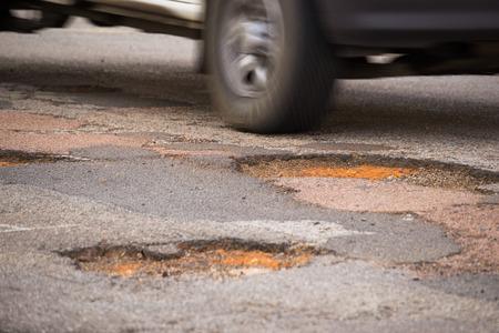 Moving car close to drive into a big pothole