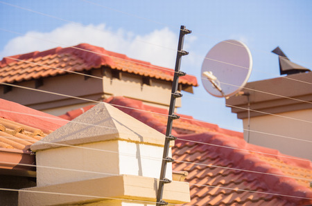 Protection for your home with high wall and electric fencing and a blurred tiled roof of a house and blue sky in background with satellite dish