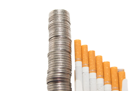 cigarette pack: Pile of silver coins and a pack of cigarettes isolated on white