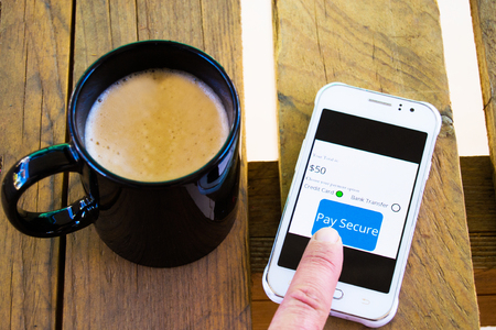 Secure online payment and calm concept on a cellphone with a finger to press a button with foamy cup of coffee next to it on a wooden table