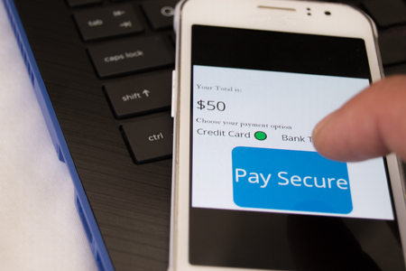 Pay secure online concept of cellphone on latop keyboard with different payment options to choose from with persons finger about to make a transaction Stockfoto