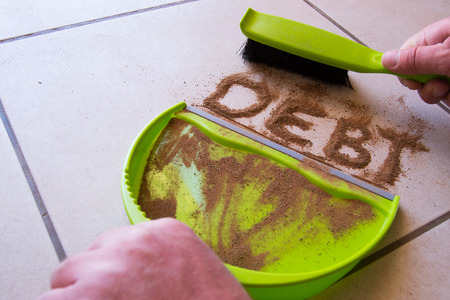 Get rid of debt with debt written in dirt on a floor and a person is about to sweep the debt dirt in a dust pan using a small hand broom Stockfoto