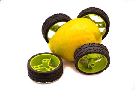Yellow lemon car with green and black wheels with single, broken wheel that fell off isolated on white Stockfoto