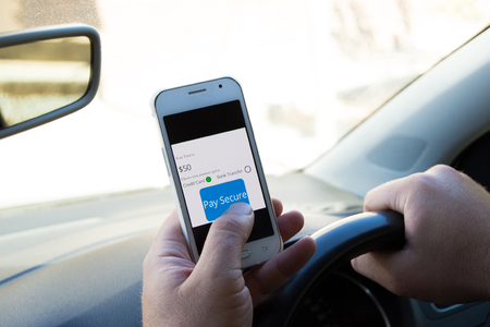 Secure online payment in a car using a cellphone while driving with persons finger pressing a pay secure button Stockfoto