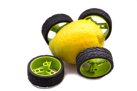 Broken lemon car with a wheel that fell with green and black wheels isolated on white Stockfoto