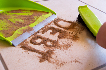 Clean your debt concept with debt written in dirt on a floor and a person is about to sweep the debt dirt in a dust pan using a small hand broom
