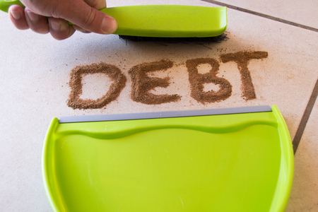 Debt concept with debt written in dirt on a floor and a person is about to sweep the debt dirt in a dust pan using a small hand broom Stockfoto