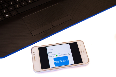 Smartphone displaying secure online payment platform next to laptop keyboard on white Stockfoto