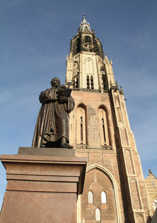 milion: Statue of Hugo Grotius (Hugo de Groot) before the New Church (Nieuwe Kerk) from 1381 in Delft. Netherlands