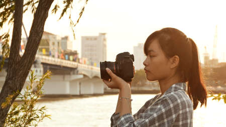 Vietnamese girl photographer takes pictures of nature in the city center at sunset Stock Photo