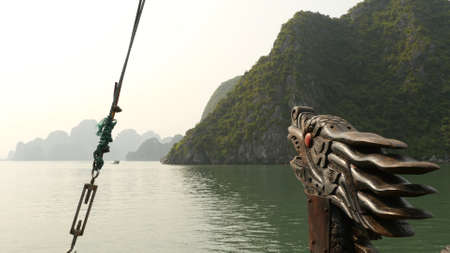 A boat with a dragons head floating in the ocean. Vietnam. Ha Long Bay. Stock Photo