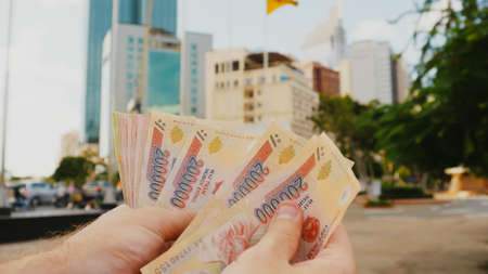 Man recounts Vietnamese money. Two hundred and one hundred thousandth of the banknote on the background of downtown Ho Chi Minh city. Stock Photo
