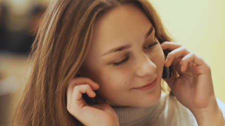 Cute young girl talking on a cell phone. Close-up.