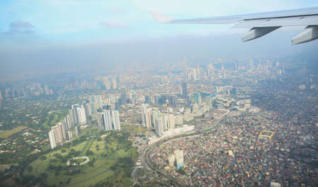 A view of the city of Manila through the window from the plane. Impressed photo of a tourist in flight over the capital. Philippines. Stock Photo