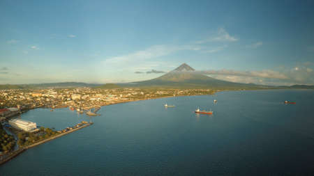 Aerial panorama of the city of Legaspi in the morning at dawn. Against the backdrop of the Mayon volcano. Seaport with boats. Imagens