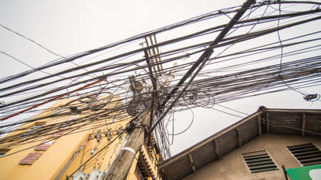 Power lines in the city. Transformers and phone lines against sky.