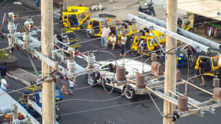 Power lines in the city. Transformers and phone lines against road in Filipino city. Stock Photo
