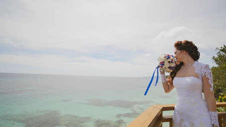 A dazzling bride enjoys happiness from the height of the balcony overlooking the ocean and reefs. Flight of love. Exotic Filipino Tropics. Shooting in motion.