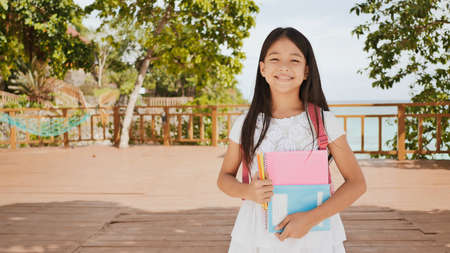 A charming philippine schoolgirl with a backpack and books in a park off the coast. A girl joyfully poses, raising her hands up with textbooks in her hands. Warm sunny day. Stock Photo