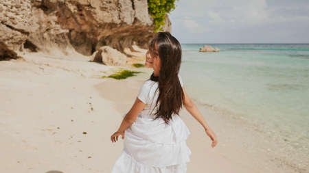A charming and happy philippine teenage girl in a white summer dress is running along a tropical beach near the rocks. She is happily spinning. Childhood. Recreation.