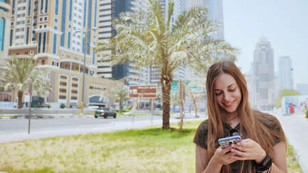 The girl dials a number or message on the smartphone against the backdrop of the city streets of Dubai. Stockfoto - 115475238