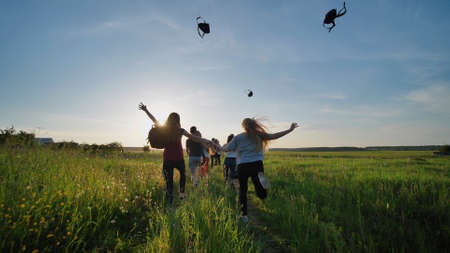 Happy senior pupils flee and toss their portfolios against the sunset. Happy ending school days. Slow motion.