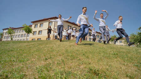 Happy graduates of the Russian school appear from behind the hill and run towards happiness.