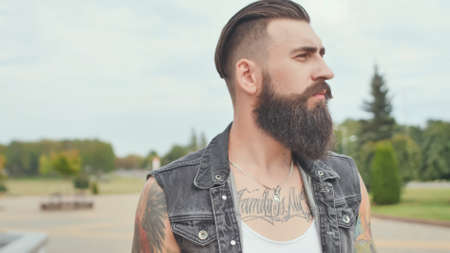 A brutal bearded man with tattoos walks through the city with a black bag.