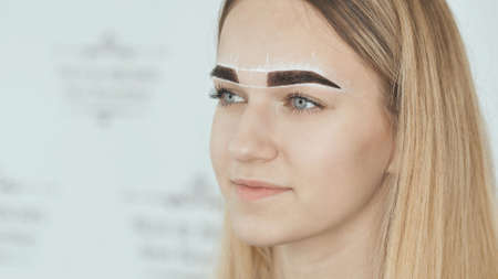 Create permanent eyebrow makeup. Marking the shape of the eyebrows.