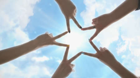 People forming star shape with their fingers against the blue sky with shining rays of the sun.