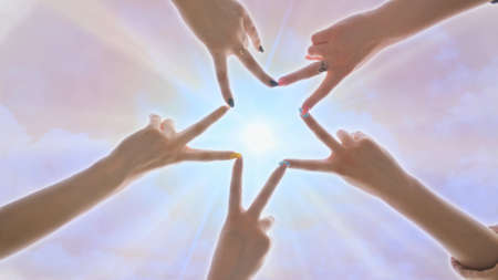 People forming star shape with their fingers against the backdrop of a pink magical sky with shining rays of the sun.