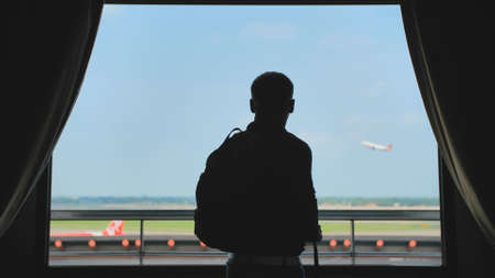A young man with a backpack on his back watches the airplane take off from the window of his hotel room and goes further.