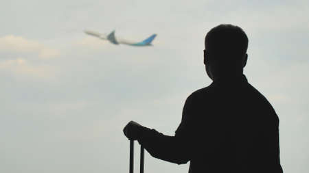 A young man with luggage is watching the take-off of the plane and then landing on the airplane. Stockfoto