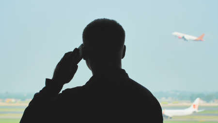 Silhouette of a young guy talking on the phone on the background of an airplane taking off.
