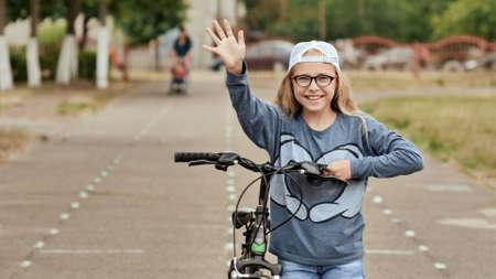 Ein elfjähriges Mädchen fährt gut gelaunt Fahrrad und zeigt nach einem Halt Daumen hoch.