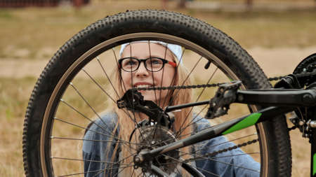 An eleven-year-old girl twists and looks at the wheel of her bicycle.