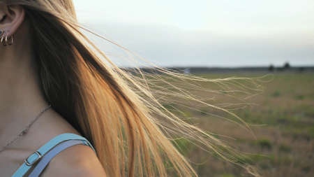 Long hair of the brown-haired young girl scatter in the wind in the sunshine rays of the evening