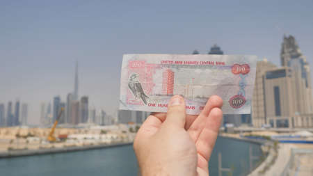 A man holds a banknote of 100 dirhams in the hands of the city of Dubai. Money of the United Arab Emirates. Stock Photo
