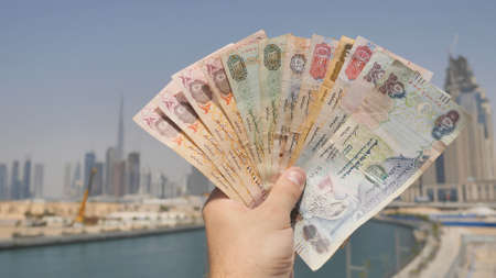 A man holds in his hand the money of the Arab Emirates. Hand close-up.